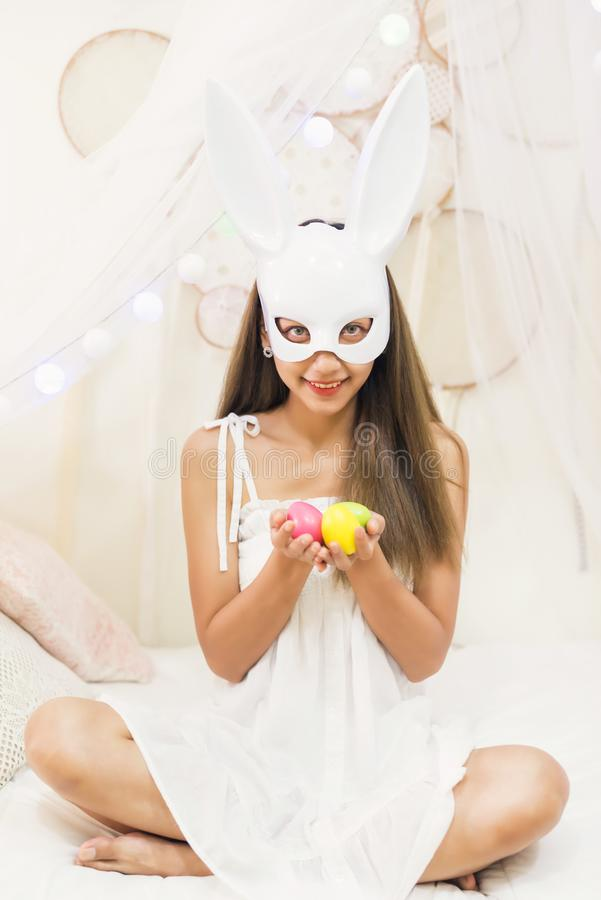 Brunette woman with bunny mask hold easter eggs. Brunette attractive woman with white rabbit bunny mask hold colorful easter eggs on hands in bedroom. Happy girl stock photo