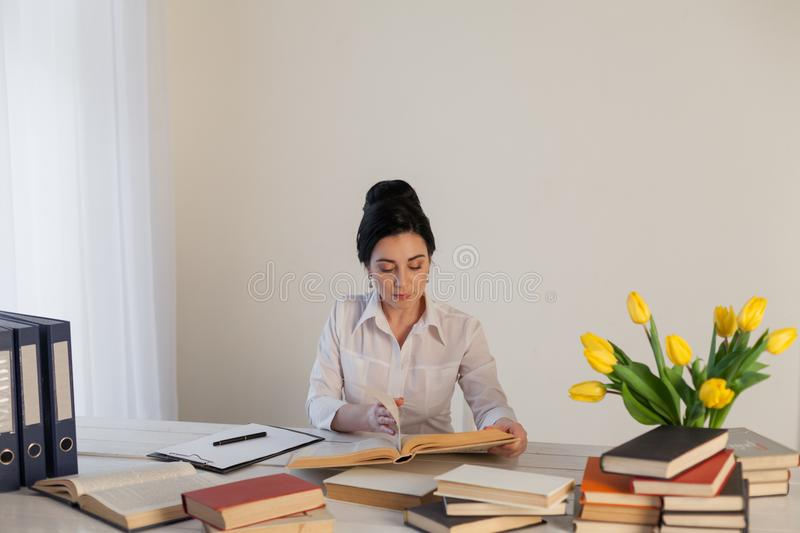 Brunette woman in a business suit reads books in the Office royalty free stock images