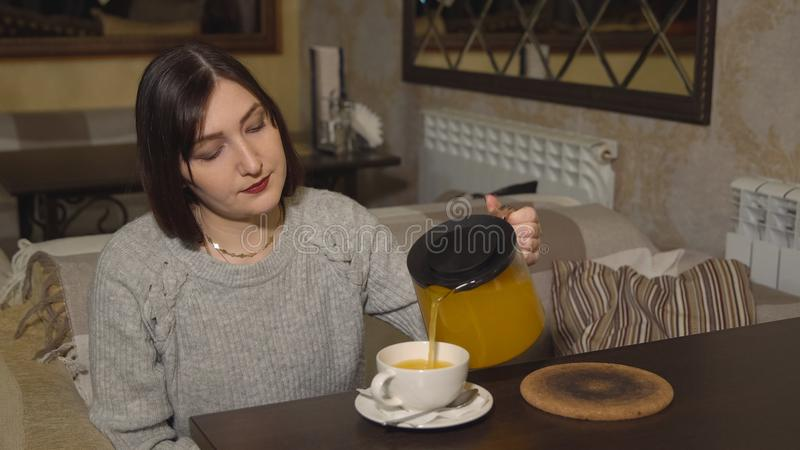 Brunette woman in a cafe pours vitamin tea royalty free stock image