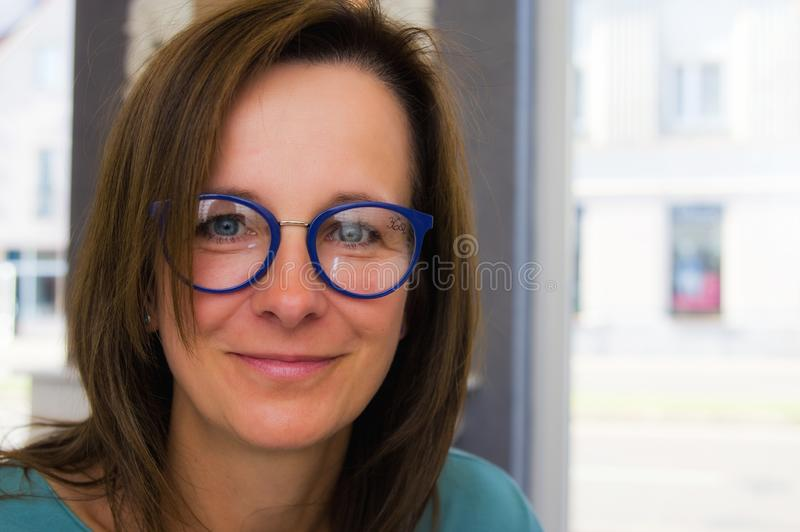 Brunette woman choosing and buying eyeglasses in optician salon or shop royalty free stock photography