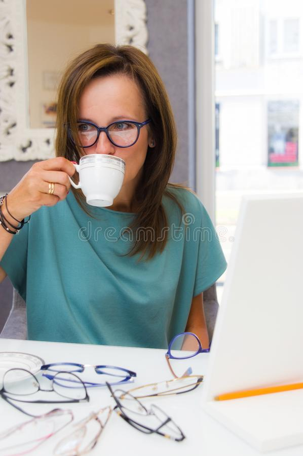 Brunette woman choosing and buying eyeglasses in optician salon or shop royalty free stock photos