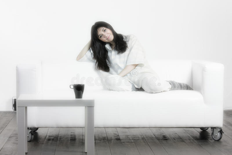 Brunette woman on couch stock photography
