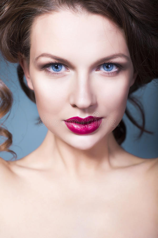 Brunette woman with creative make up violet eye shadows full red lips, blue eyes and curly hair with her hand on her face stock photography