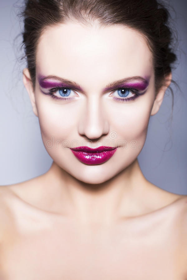 Brunette woman with creative make up violet eye shadows full red lips, blue eyes and curly hair with her hand on her face stock photos