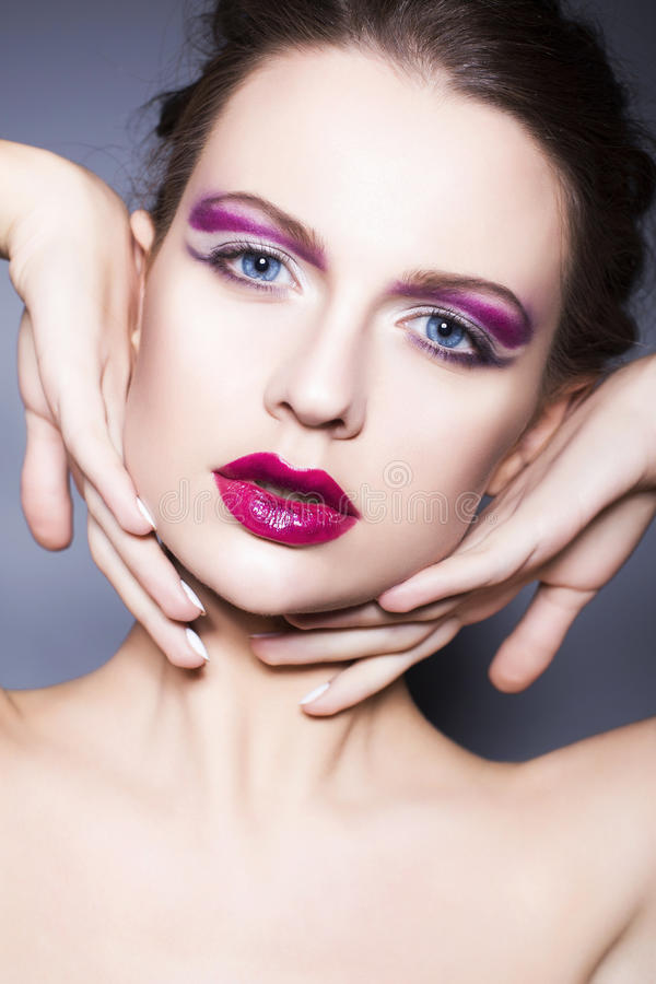 Brunette woman with creative make up violet eye shadows full red lips, blue eyes and curly hair with her hand on her face royalty free stock photo