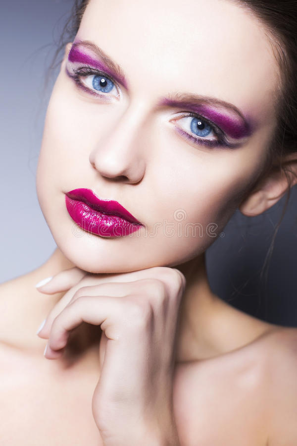 Brunette woman with creative make up violet eye shadows full red lips, blue eyes and curly hair with her hand on her face royalty free stock images