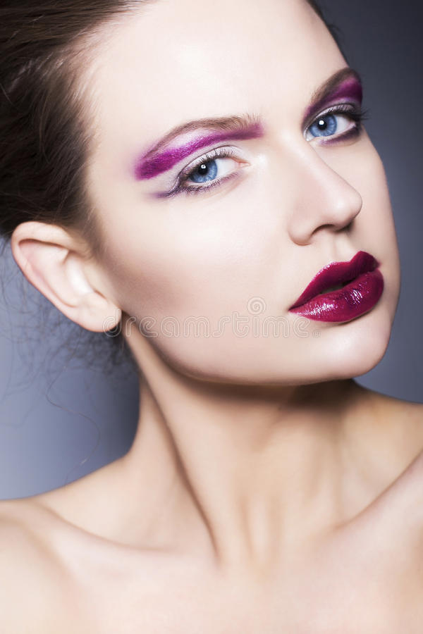 Brunette woman with creative make up violet eye shadows full red lips, blue eyes and curly hair with her hand on her face stock image
