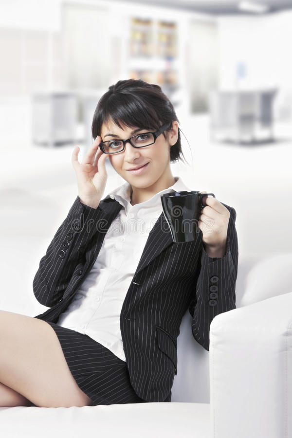 Brunette woman with cup on sofa at office stock image