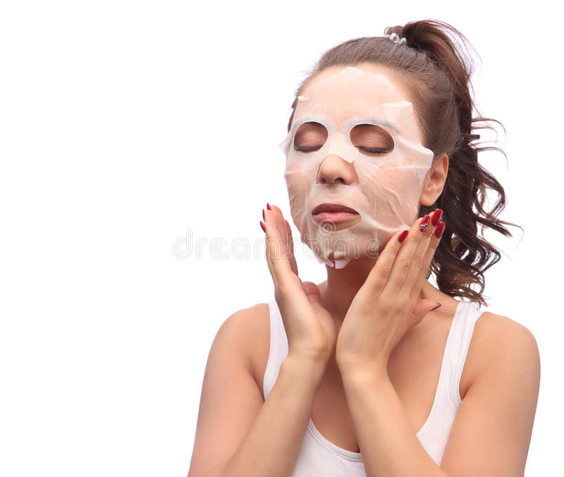 Brunette woman doing facial mask sheet. Beauty and Skin Care Concept. Girl applying mask to her face, studio shot royalty free stock photo