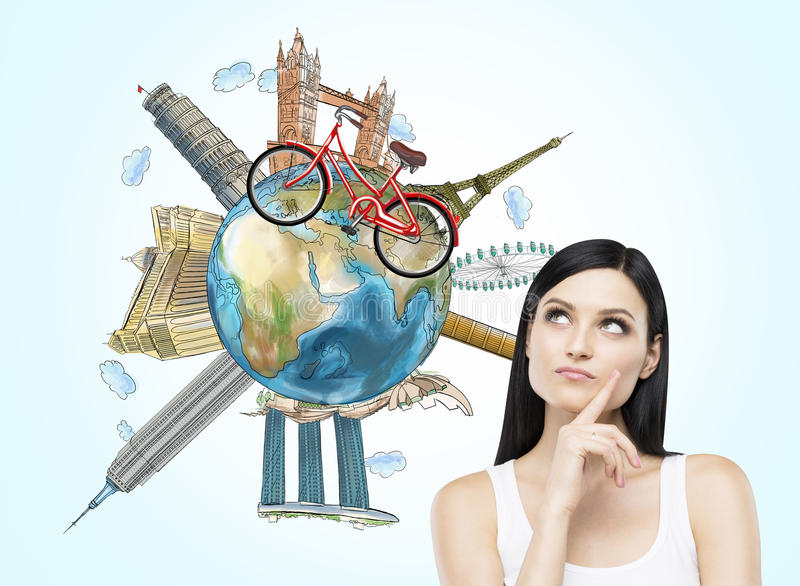 A brunette woman is dreaming about travelling. The globe with the most famous places in the world. A model of bicycle crosses of t royalty free stock photos