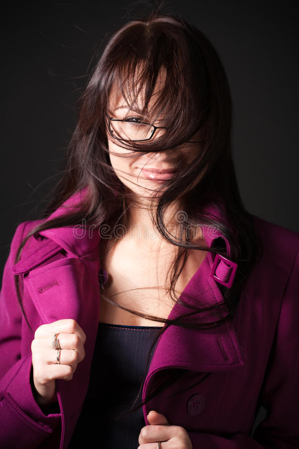 Brunette woman dress pink coat under the high wind stock image