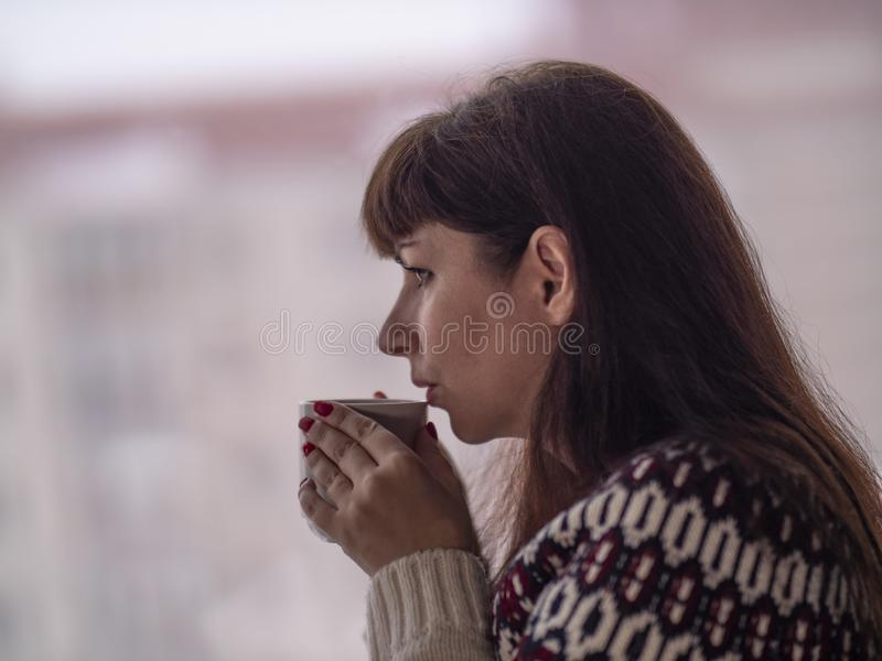 Young brunette woman drinks coffee and looks out the window thoughtfully stock photo