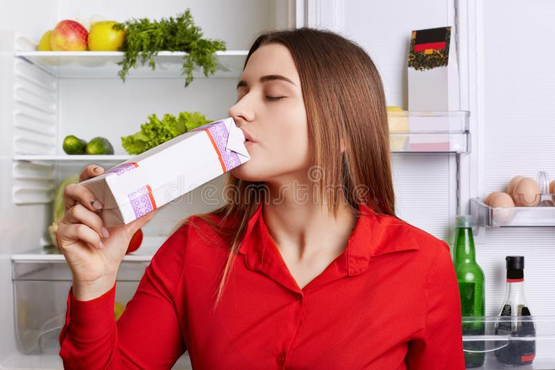 Brunette woman drinks milk from papaer container, feels fresh and healthy as eats nutritious food, stands near fridge with product royalty free stock photo