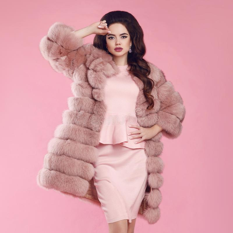 Brunette Woman in fur coat over pink. fashion studio photo of go. Rgeous sensual woman with long wavy hair in luxurious dress and fur coat royalty free stock images