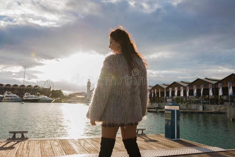 Brunette woman with fur coat portrait standing outside, with the sun in the background royalty free stock photo