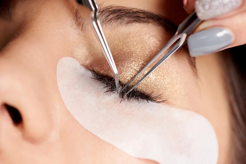 Brunette woman is getting eyelash extensions in a salon royalty free stock photos