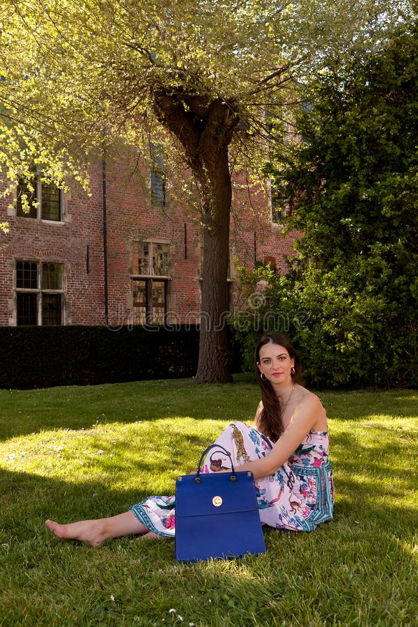 Brunette woman grass tree, Groot Begijnhof, Leuven, Belgium royalty free stock photos