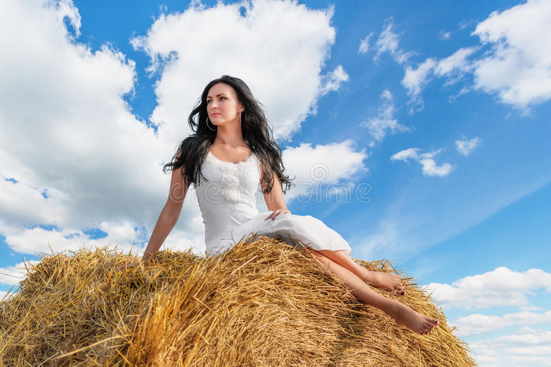 Brunette woman on hay bale. Beautiful brunette woman sitting on hay bale in warm summer day royalty free stock images