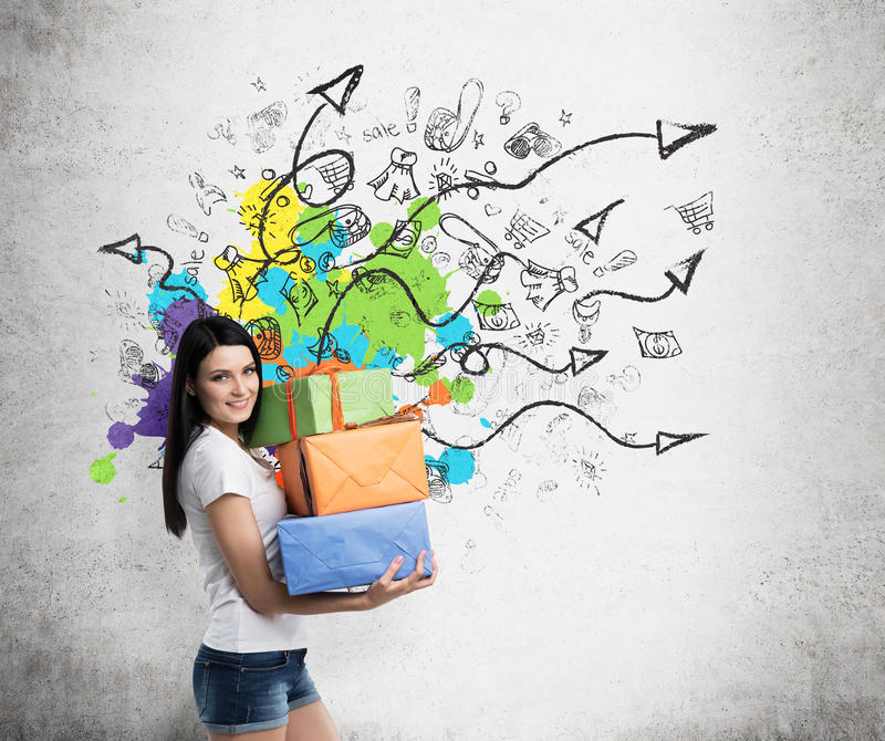 A brunette woman is holding three colourful gift boxes. Drawn sketch on the wall with arrows and shopping icons. royalty free stock photography
