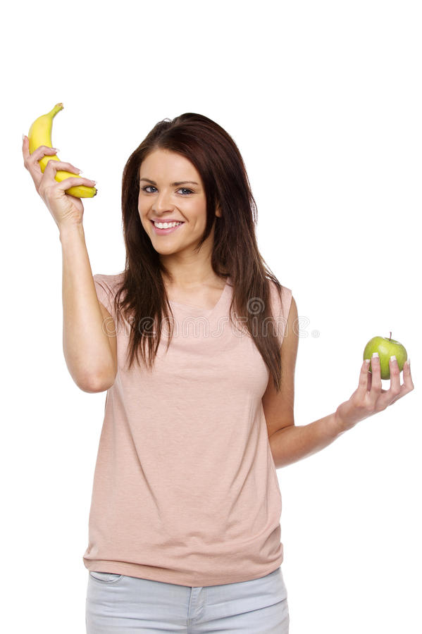 Brunette woman holding up an apple and banana stock image