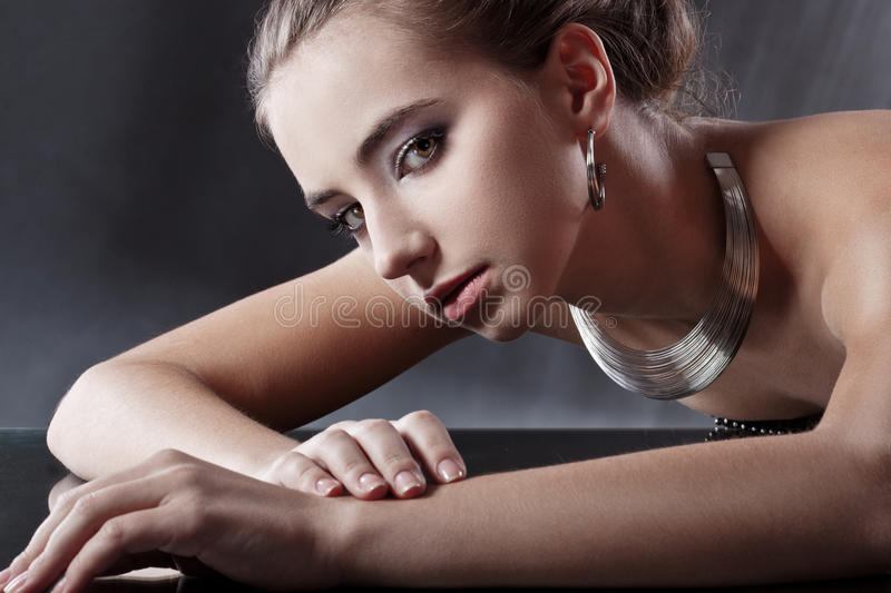 Brunette woman with jewellery looking at camera royalty free stock image