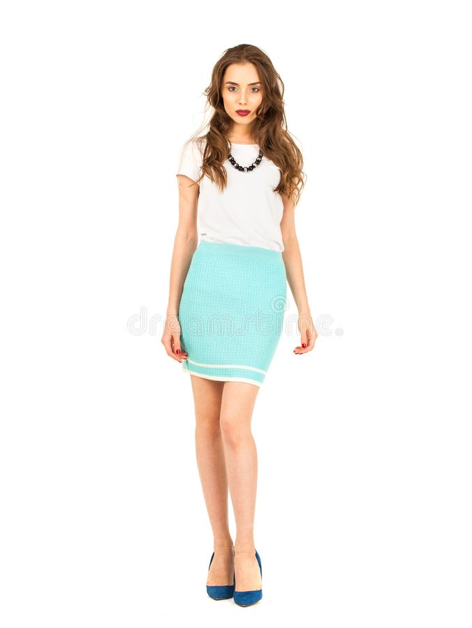 Brunette woman in a knitted turquoise skirt and white t-shirt. Full body fashion model. Young brunette woman in a knitted turquoise skirt and white t-shirt royalty free stock photo