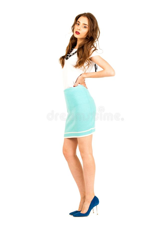 Brunette woman in a knitted turquoise skirt and white t-shirt. Full body fashion model. Young brunette woman in a knitted turquoise skirt and white t-shirt royalty free stock photos