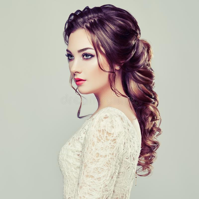 Brunette woman with long and shiny curly hair. Beautiful Model Lady with Curly Hairstyle. Care and Beauty Hair products. Care and Beauty of Hair stock image