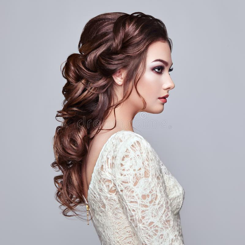 Brunette woman with long and shiny curly hair. Beautiful Model Lady with Curly Hairstyle. Care and Beauty Hair products. Care and Beauty of Hair stock photos