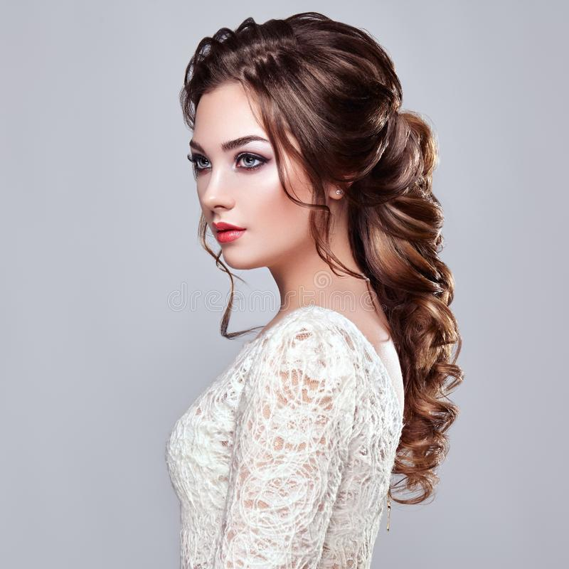 Brunette woman with long and shiny curly hair. Beautiful Model Lady with Curly Hairstyle. Care and Beauty Hair products. Care and Beauty of Hair stock images