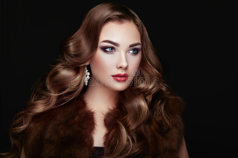 Brunette woman with long shiny wavy hair. Brunette Girl with Long and shiny Curly Hair. Beautiful Model Woman in the Fur Coat Care and Beauty Hair products stock image