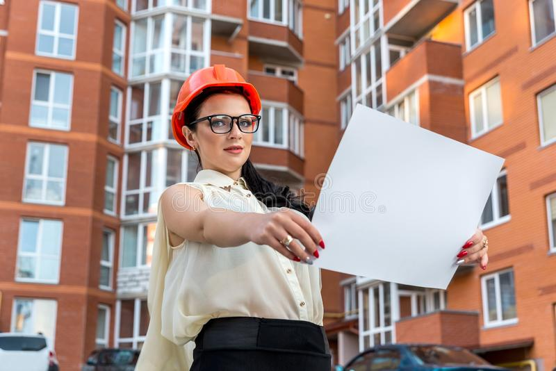 Brunette woman looking at building plan on construction site royalty free stock photo