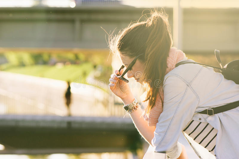 Brunette woman, looking down on the bridge, by sticking sunglass stock photos