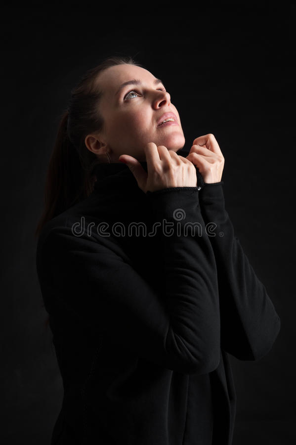 Brunette woman looking up in darkness. praying stock photo