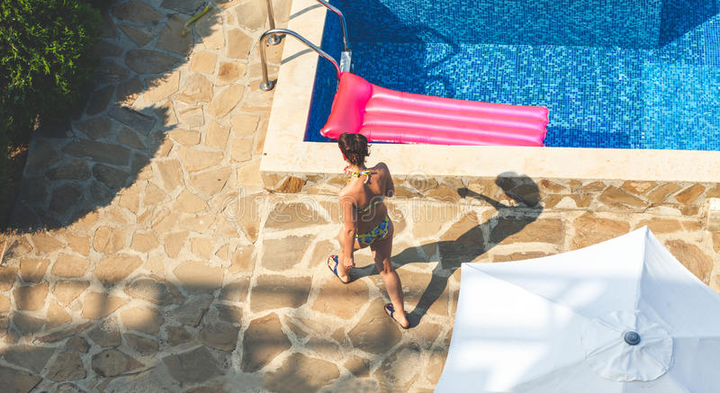 Brunette woman near swimming pool at sunny day stock photo