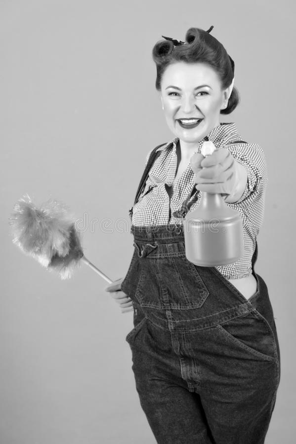 Brunette woman in pin-up style with soft duster and spray bottle royalty free stock images