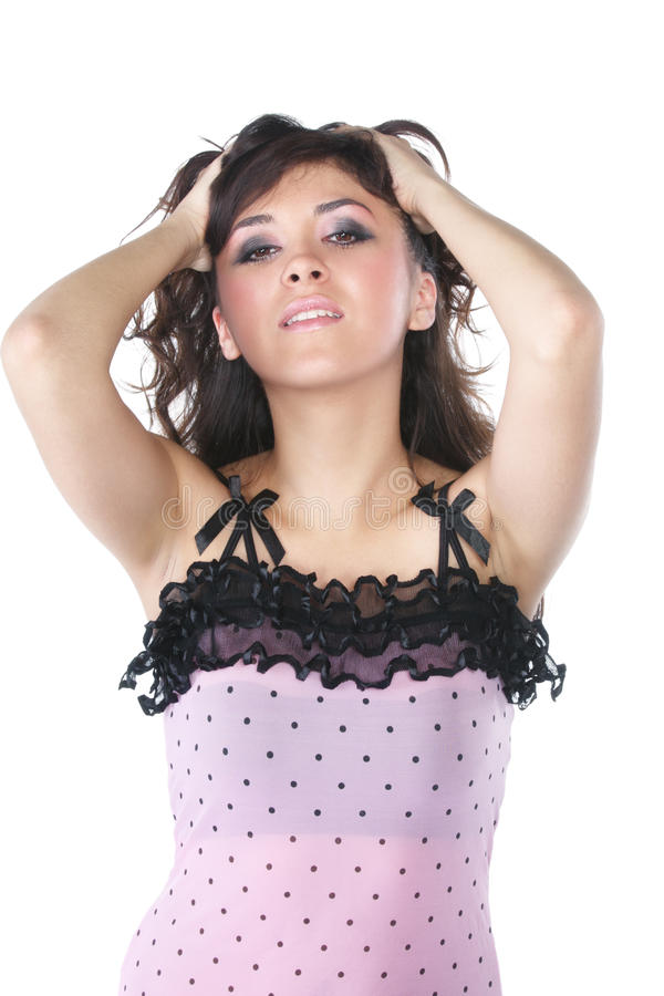 Brunette woman in pink touching hair stock images