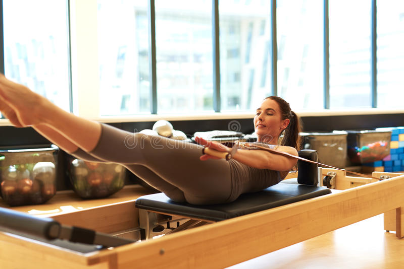 Brunette Woman Practicing Pilates in Studio stock images