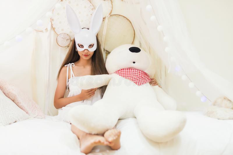 Brunette woman with rabbit mask hold big bear. Brunette attractive woman with white rabbit bunny mask hold white big bear doll on bedin bedroom. Happy girl royalty free stock photos
