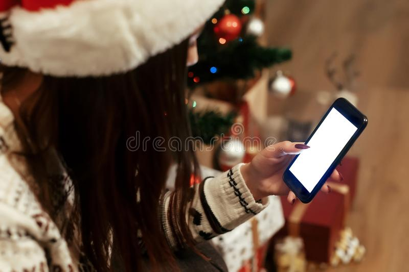 Brunette woman in red santa hat and reindeer sweater texting on. Her smartphone while decoration christmas tree with colorful ornaments, advertising concept royalty free stock photography