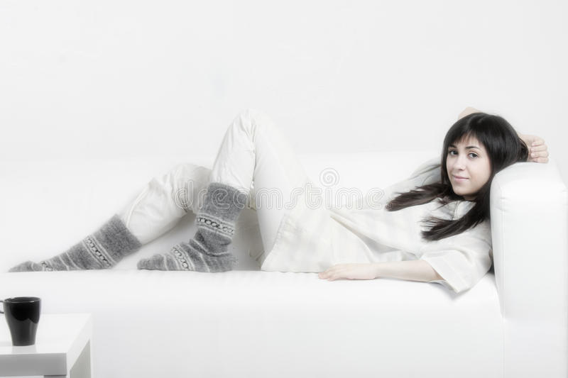 Brunette woman relaxed on couch stock photo