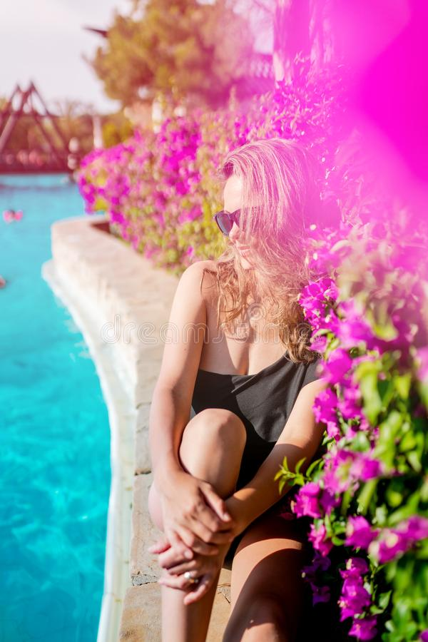 brunette woman relaxing and smiling at swimming pool during summer holiday stock image