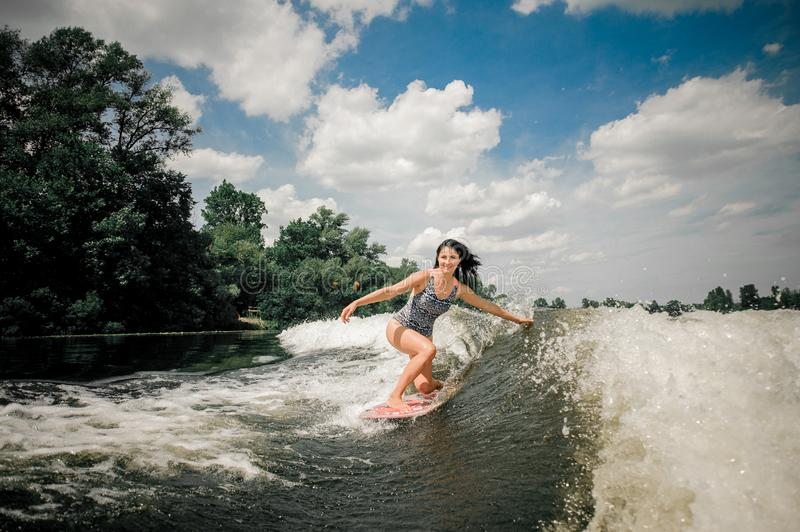 Brunette woman riding wakeboard on wave of motorboat stock photo