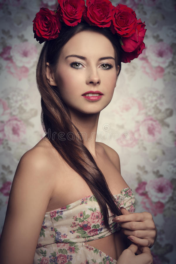 Brunette woman with roses on head. Close-up portrait of lovely girl with long smooth brown hair and sprig dress posing with red roses on the head and natural royalty free stock images