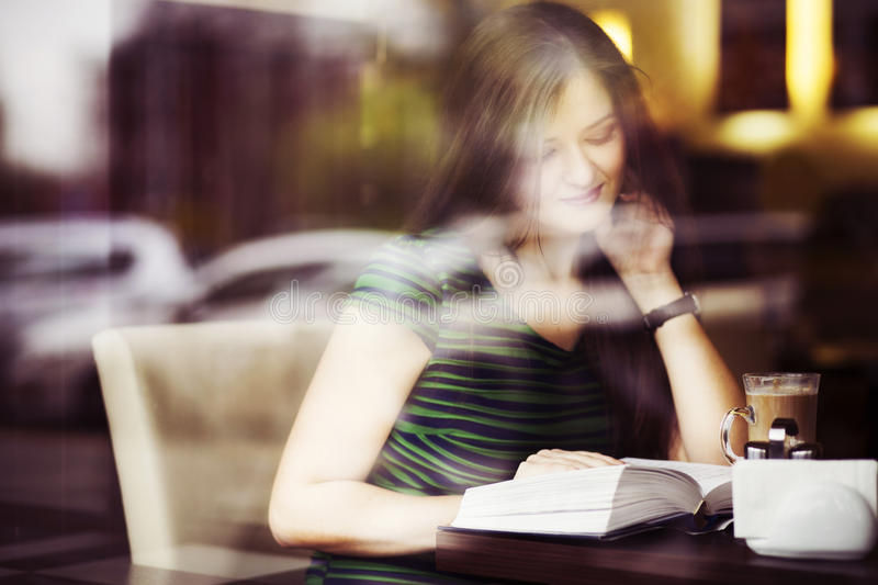 Brunette woman sitting at the cafe reading book, studing and drinking coffee stock image