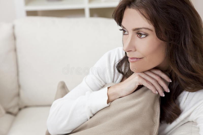 Brunette Woman Sitting Thinking At Home on Sofa stock photo