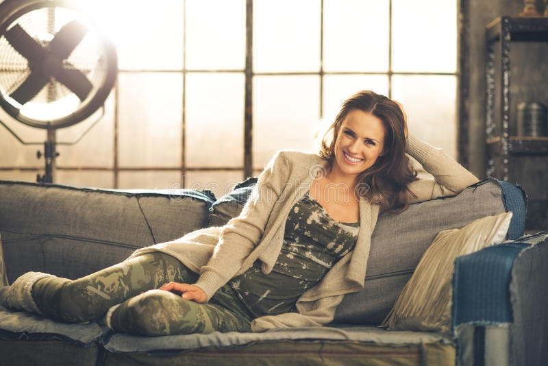 A brunette woman is smiling, relaxing on a sofa. Feet curled under her, wearing comfortable clothing, leggings, and a cardigan. Industrial chic ambiance and royalty free stock photography