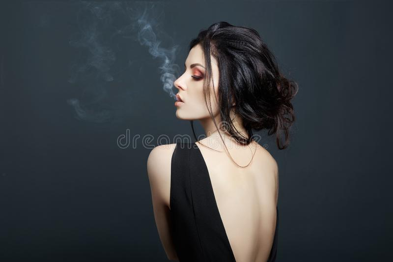 Brunette woman Smoking on dark background in black dress. Erotic girl.  stock photos