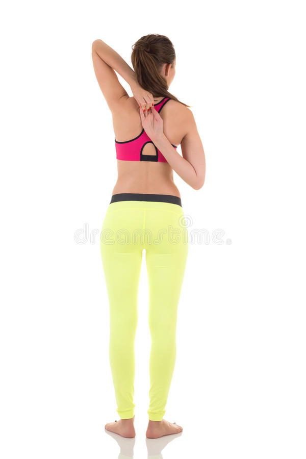Brunette woman standing and doing exercises for muscles of the back. royalty free stock photos