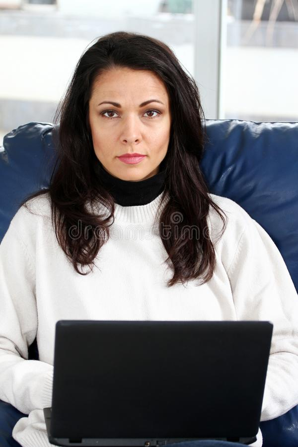 Brunette woman in sweater sitting on the couch with laptop computer royalty free stock photos